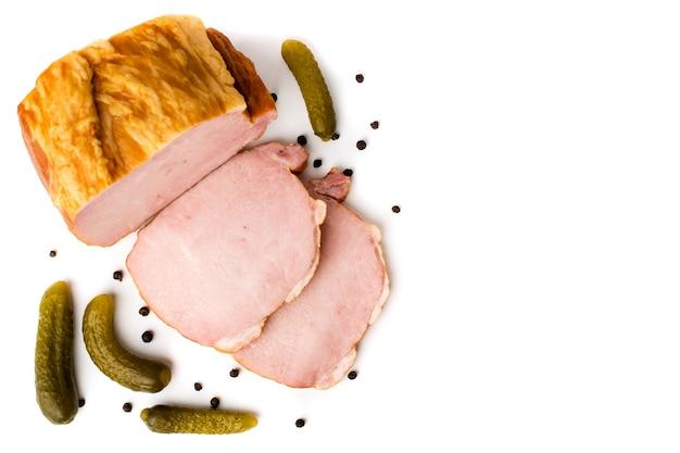 Morceau de viande fumée et concombre au poivre noir sur fond blanc, isolé. la vue du haut.
