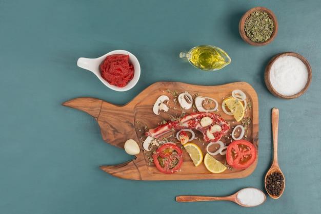 Morceau de viande non cuit avec légumes, huile et épices sur table bleue.