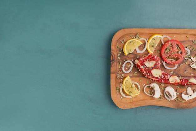 Morceau de viande non cuit avec des légumes sur table bleue.