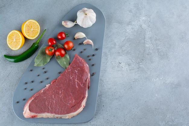 Morceau de viande rouge crue et légumes frais sur une planche à découper.