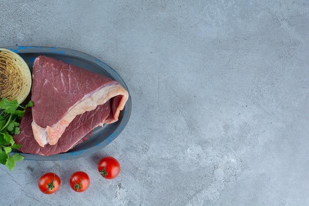 Morceau de viande rouge crue placé sur une assiette bleue.