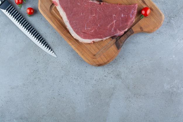 Morceau de viande rouge crue placé sur une planche à découper en bois.