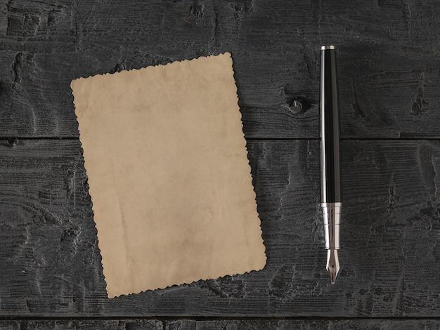 Un morceau de vieux papier et un stylo-plume sur une table en bois. papier à lettres rétro. mise à plat la vue du haut.