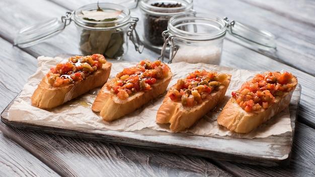 Morceaux de baguette sur papier. pots avec assaisonnements. bruschetta aux légumes cuits au four. repas savoureux sur table en bois.