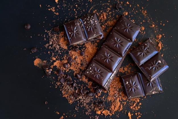 Morceaux de barre de chocolat amer cassé et poudre de cacao sur la vue de dessus de surface sombre