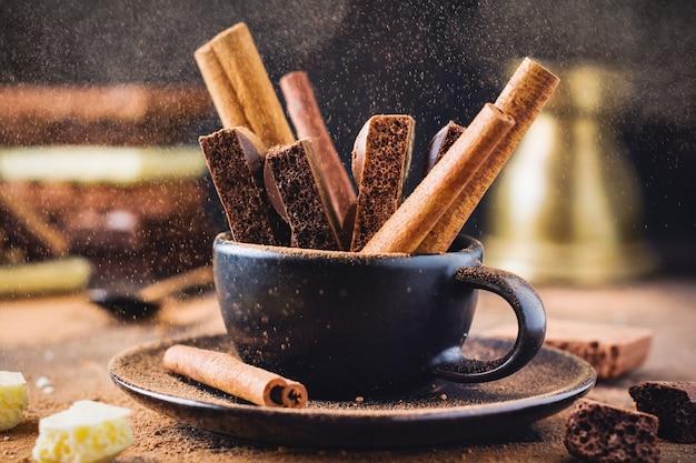 Morceaux de bâtons de chocolat et de cannelle poreux dans une tasse de café noir sur une vieille surface sombre. mise au point sélective.