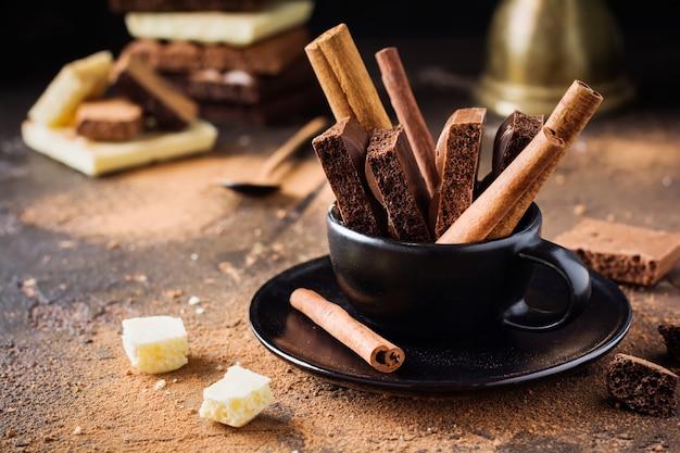Morceaux de bâtons de chocolat et de cannelle poreux dans une tasse de café noir sur une vieille surface sombre