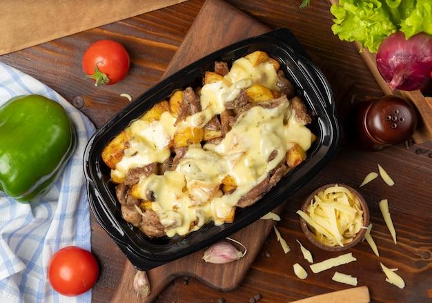 Morceaux de bœuf rôtis grillés et tranches de pommes de terre au fromage fondu à la crème