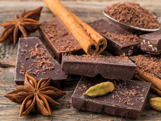 Morceaux brisés de chocolat, anis étoilé, bâtons de cannelle, miettes sur fond en bois ancien