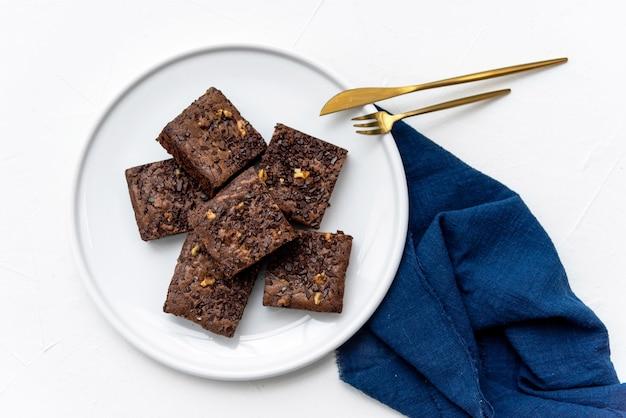 Morceaux de brownie frais sur plaque blanche avec des couverts dorés sur une serviette bleue