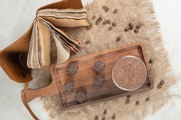 Morceaux de café et de chocolat sur planche de bois avec haricots et cahier.