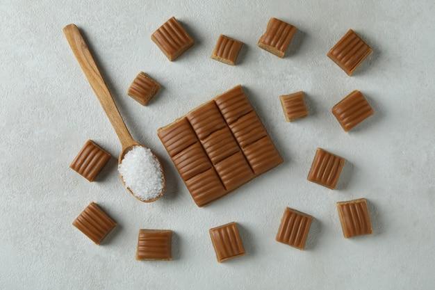 Morceaux de caramel et cuillère avec du sel sur fond texturé blanc