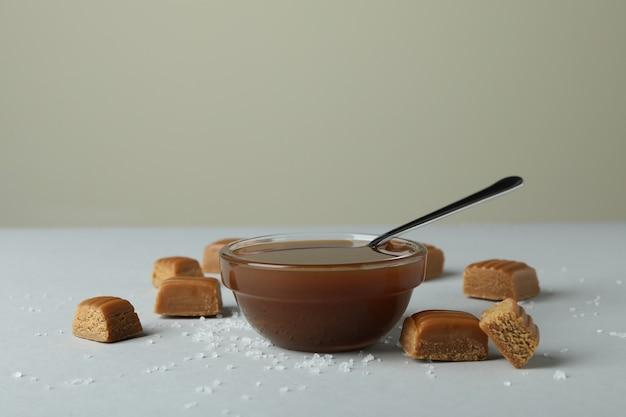 Morceaux de caramel salé et bol de sauce sur table gris clair