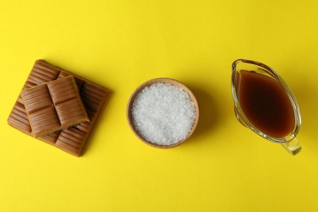 Morceaux de caramel, sauce et bol de sel sur fond jaune