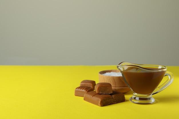 Morceaux de caramel, sauce et bol de sel sur table jaune