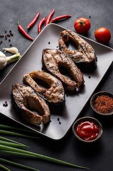 Morceaux de carpe grillée sur une assiette avec poivrons tomites oignons rouges ail