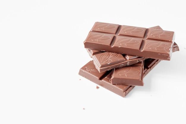Morceaux de chocolat au lait isolés sur fond blanc