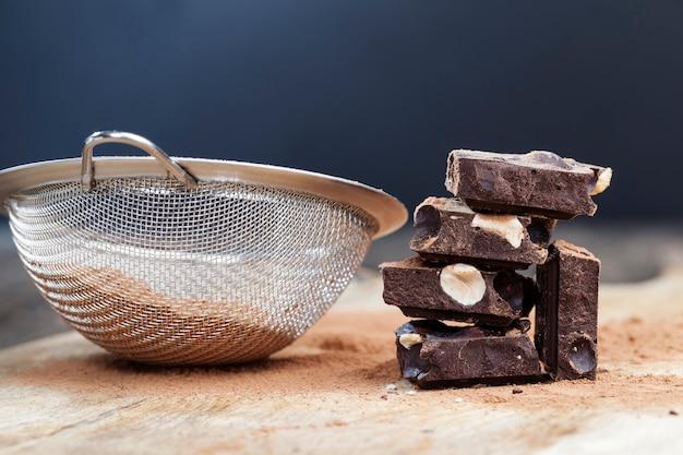 Morceaux de chocolat aux noisettes avec cacao et sucre, divisés en morceaux barre de chocolat aux noix entières, chocolat sucré aux noix cassées en morceaux
