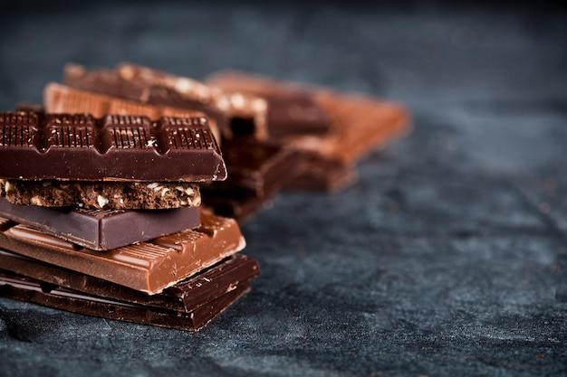 Morceaux de chocolat brisé empilés sur un tableau noir.