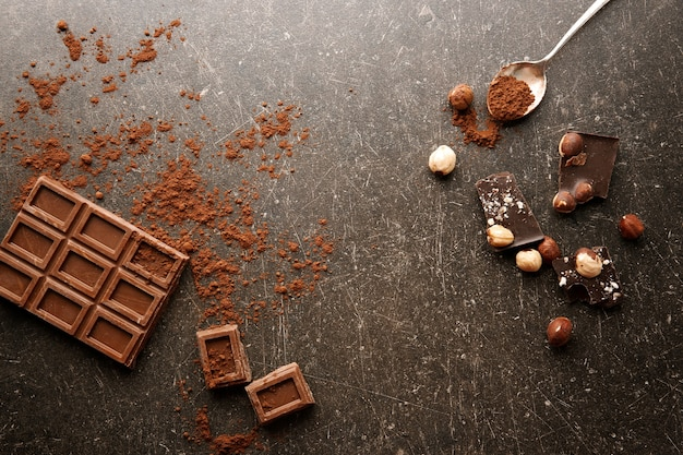 Morceaux de chocolat cassés avec cuillère sur table