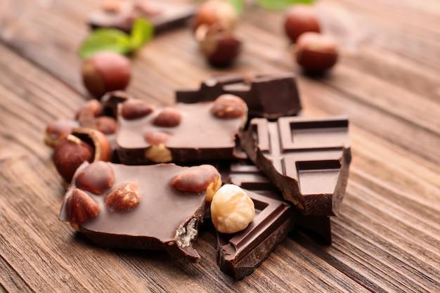 Morceaux de chocolat cassés avec des noix et des feuilles de menthe sur table en bois