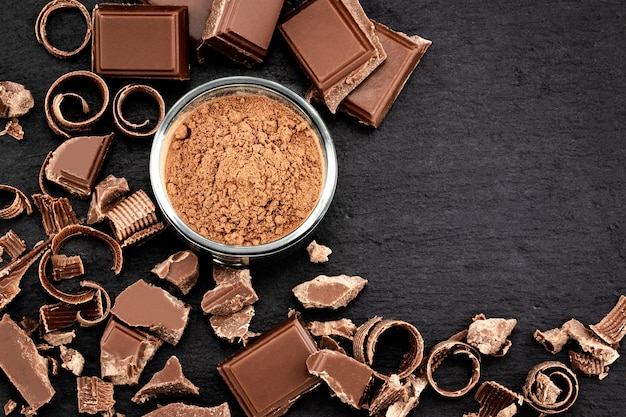 Morceaux de chocolat cassés et poudre de cacao sur fond sombre.