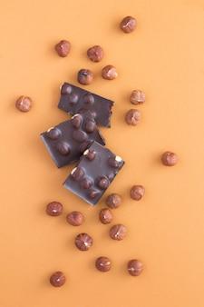 Morceaux de chocolat noir aux noisettes sur le brun clair