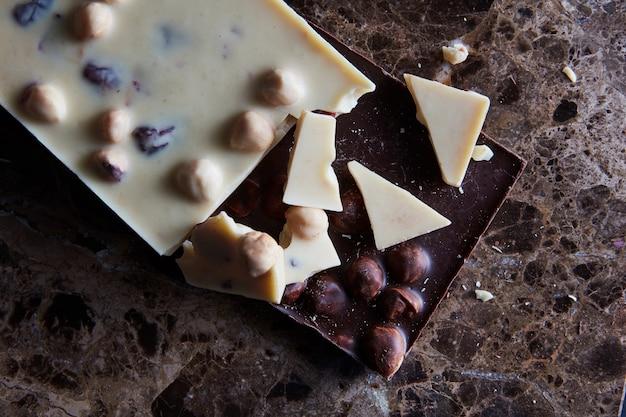 Morceaux de chocolat noir et blanc isolés sur un fond de marbre noir