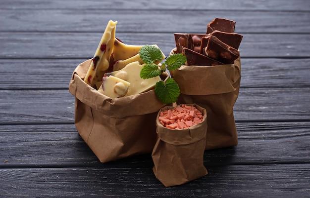Morceaux de chocolat noir, blanc et rose dans un sac en papier