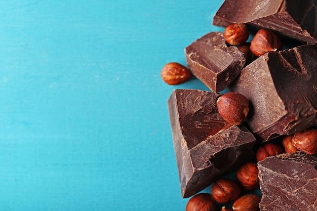 Morceaux de chocolat noir avec des noix sur fond de bois de couleur