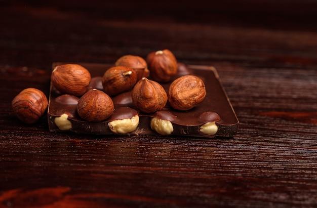Morceaux de chocolat et de noix sur une table en bois sur fond noir