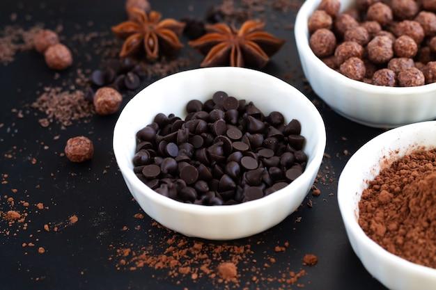 Morceaux de chocolat et poudre de cacao dans des bols sur une table en ardoise sombre, surface des ingrédients de cuisson des desserts