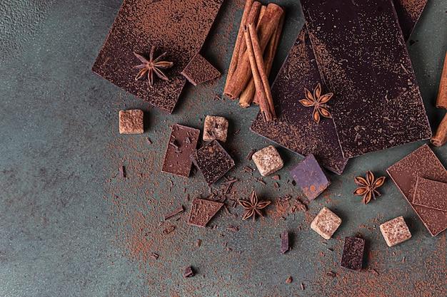Morceaux de chocolat, poudre de cacao, épices et cassonade. concept d'ingrédients de cuisine.