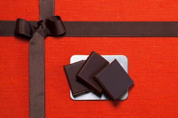Morceaux de chocolat sur toile de lin orange avec ruban brun et arc, gros plan