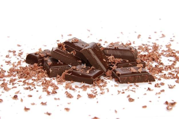 Morceaux de chocolats et petits copeaux sur une surface blanche