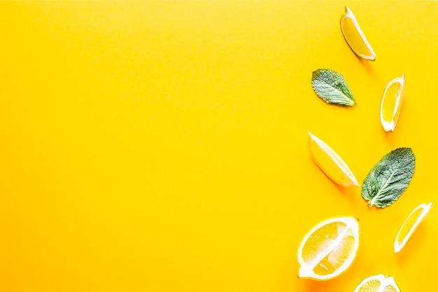 Morceaux de citron, citron vert et menthe verte sur fond jaune