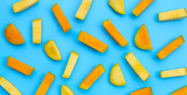 Morceaux coupés de mangue sur fond bleu.