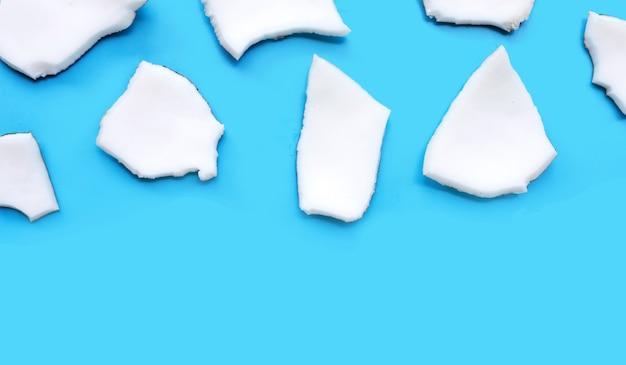 Morceaux coupés de noix de coco sur fond bleu. vue de dessus