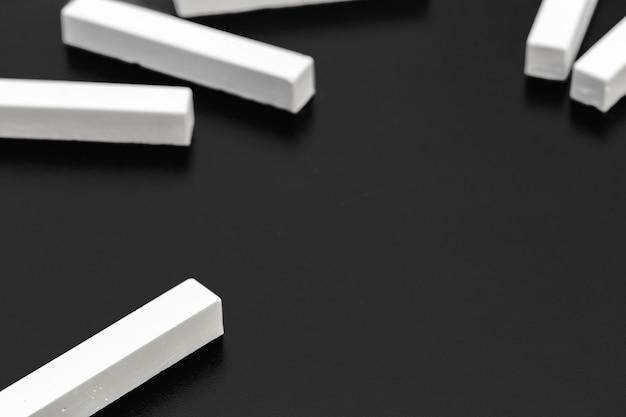 Morceaux de craie blanche photographiés sur un tableau noir
