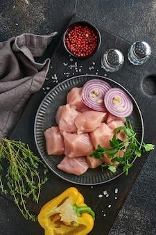 Morceaux crus d'ingrédients de viande de poulet sur planche de bois, épices, herbes et légumes sur fond gris foncé. ingrédients crus pour goulasch ou shish kebab. vue de dessus. espace de copie gratuit.