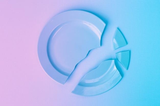 Morceaux de cymbale cassée empilés en une seule pièce, dégradé rose et bleu. le concept de rupture des relations, divorce, destruction.