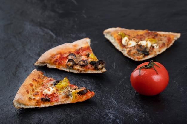 Morceaux de délicieuses pizzas aux tomates rouges fraîches placées sur un fond noir.