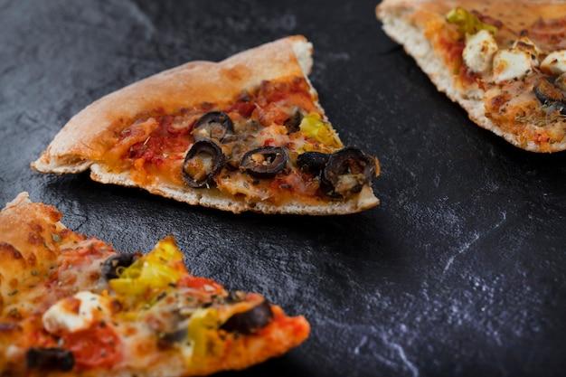 Morceaux de délicieuses pizzas placés sur un fond noir.