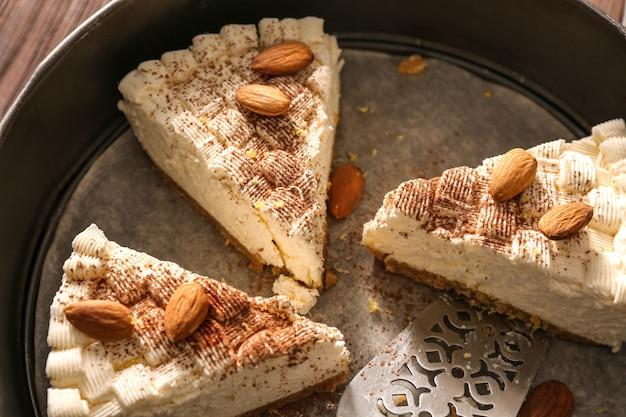 Morceaux de délicieux cheesecake aux amandes dans un plat allant au four