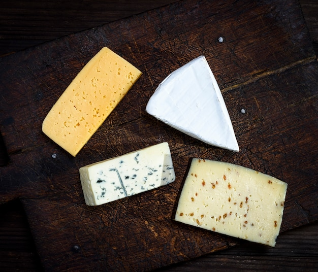 Morceaux de différents fromages sur une planche en bois marron: