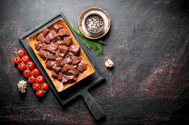 Morceaux de foie cru sur une planche à découper avec des tomates et des épices.