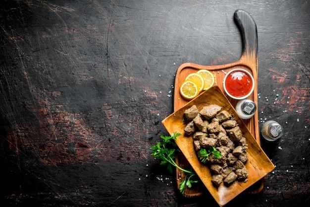 Morceaux de foie cuit sur une planche à découper avec du citron, des herbes et de la sauce tomate