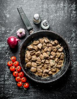 Morceaux de foie frit dans une poêle avec des oignons, de l'ail et des tomates. sur une surface rustique sombre