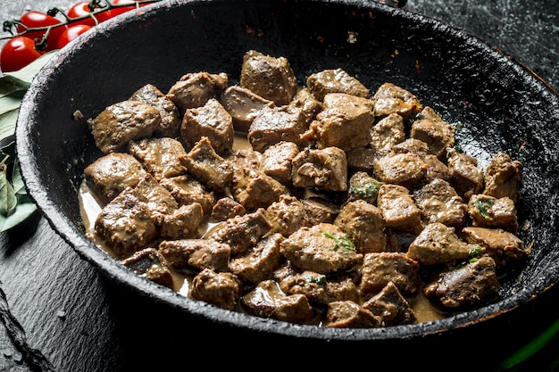 Morceaux de foie frit. sur table rustique sombre