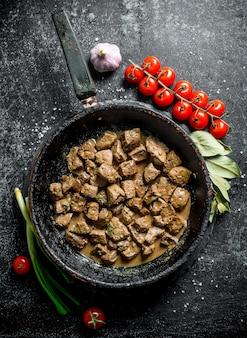 Morceaux de foie frits à l'ail, tomates cerises et feuille de laurier. sur une surface rustique sombre
